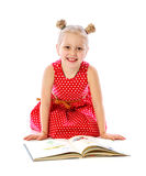 Portrait of a little girl reading books, sitting on the floor Royalty Free Stock Photos