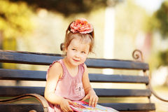 Portrait of a little girl reading a children's book on a park be Royalty Free Stock Photos