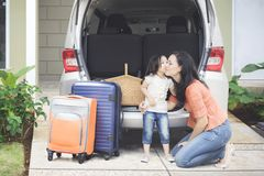 Girl kissing her mother near the car. Portrait of little girl ready to holiday travel while kissing her mother near the car, shot in the house garage Stock Photo