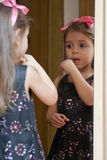 Portrait of little girl reflected in mirror. Fashionable little girl in black dress with pink bow paints her lips. Reflection in the mirror Royalty Free Stock Photo