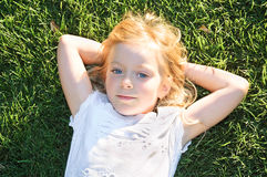 Portrait of  little girl relaxing on green grass Stock Image
