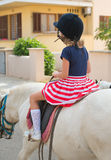Portrait of little girl riding pony. Royalty Free Stock Image