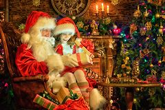 Portrait of little girl with Santa Claus in room royalty free stock photography