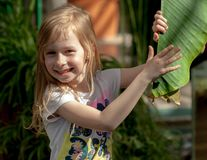Portrait, little girl of seven years, holds large leaf of palm tree royalty free stock photos