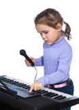 Portrait of a little girl sings and plays the piano Stock Photography
