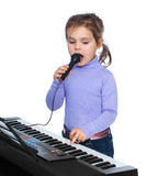 Portrait of a little girl sings and plays the piano Stock Photo