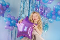 Portrait of little girl sits with color balloons (star). Portrait of Pretty little girl sits with color balloons (star Stock Photo