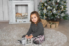 Portrait of little girl sits on a floor and plays with wooden toy in Christmas at home Royalty Free Stock Photos