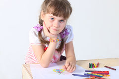 Portrait of little girl sits at table with paper sheets Royalty Free Stock Images