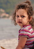 Portrait of a little girl, sitting on a beach Royalty Free Stock Image