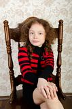 Portrait of little girl sitting on a chair Royalty Free Stock Image