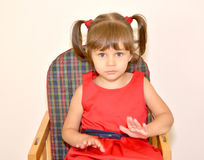 Portrait of the little girl sitting on a children's chair Royalty Free Stock Photography