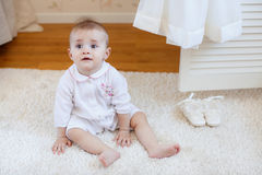 Portrait of a little girl sitting on the floor Royalty Free Stock Images