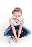 Portrait of a little girl sitting on the floor. Stock Images