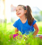 Portrait of a little girl sitting on green grass Royalty Free Stock Photo