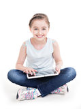 Portrait of little girl sitting with the tablet. Royalty Free Stock Images