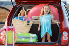 Portrait of a little girl sitting in the trunk of a car. Little girl , brunette with long curly hair , dressed in a blue summer dress ,goes on a journey to the Stock Photography