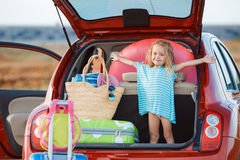 Portrait of a little girl sitting in the trunk of a car. Little girl , brunette with long curly hair , dressed in a blue summer dress ,goes on a journey to the Royalty Free Stock Photo