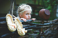 Portrait of a little girl of Slavic appearance. In the village fence royalty free stock photos