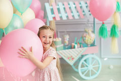 Portrait of a little girl smiles and holds a big balloon. A portrait of a beautiful little girl smiles and holds in a hands a big color balloon in the studio Royalty Free Stock Photography