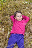 Portrait of a little girl smiling as she lies in  the grass Royalty Free Stock Images
