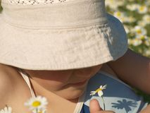 Portrait of a little girl sniffing a daisy in a beige sun hat covering her eyes stock images