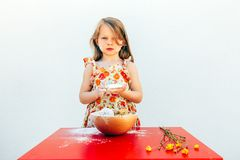 Portrait of a little girl with a soiled face flour. Isolated on white background, wearing a flower theme dress. A bowl with cookies and yellow flowers are on stock images