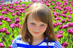 Portrait of little girl stand by lilac tulips stock photo