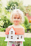 Portrait of little girl standing on grass with model of house Royalty Free Stock Image