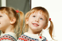 Portrait of little girl standing near the mirror Stock Photography