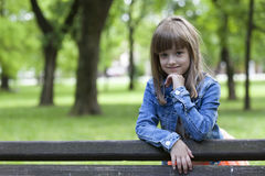 Portrait of a little girl standing next to the bench in the park. Little girl standing next to the bench in the park and looking pensively Stock Photos