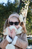 Portrait of little girl standing in winter park with hands to mouth Stock Photo