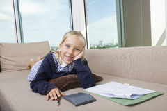 Portrait of little girl studying while lying on sofa Royalty Free Stock Photography