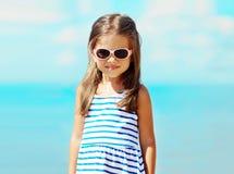 Portrait little girl in sunglasses agains Stock Photo