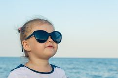 Portrait of a little girl in sunglasses by the sea stock image