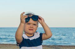 Portrait of a little girl in sunglasses by the sea stock images