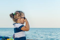 Portrait of a little girl in sunglasses by the sea royalty free stock photo