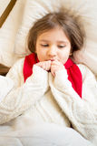 Portrait of little girl in sweater ling in bed under blanket Royalty Free Stock Photo