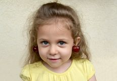 Portrait of the little girl with sweet cherry berries as earring on ears royalty free stock photography