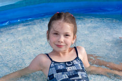 Portrait of the little girl in swimming pool. During summer vacation royalty free stock image