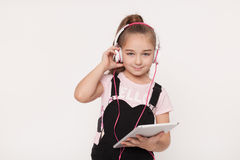 Portrait of little girl with tablet listening to audio book. Portrait of a little girl with tablet listening to audio book on white background Royalty Free Stock Photography