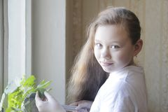 Portrait of a little girl teenager watering flowers at home. Close up royalty free stock photos