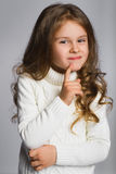 Portrait of little girl thinking, over a gray Royalty Free Stock Images