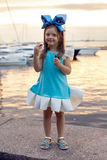 Portrait of a little girl three years with the blue bow on her head, stands near the water Stock Image