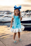 Portrait of a little girl three years with the blue bow on her head, stands near the water Stock Images