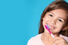 Portrait of little girl with toothbrush on color background. Space for text royalty free stock photography