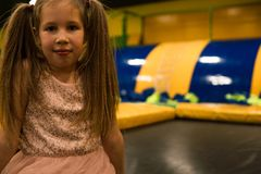 Portrait of a Little girl on a trampoline playground in kids play room.  royalty free stock images