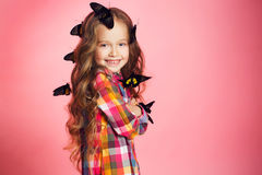 Portrait of a little girl with tropical butterflies. Royalty Free Stock Image