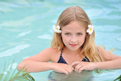Portrait of little girl. In tropical style in a swimming pool Stock Image