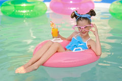 Portrait of little girl. In tropical style in a swimming pool Stock Images